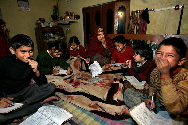 Cosins Vishal, 12, left, Shweta, 12, Kritica, 10, and  Shiram, 9, Sucheta, 7, and Rajat Sharma, 10 sit on a bed doing their homework with the help of their mother and aunt Shashi Sharma, 30, in her home in the village of Kathiada, Himachal Pradesh, India, December 9, 2006.