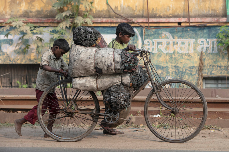 Boys push a bicycle loaded with bags of scavenged coal along Main Road in Dhanbad, Jharkhand, India, October 28, 2018.