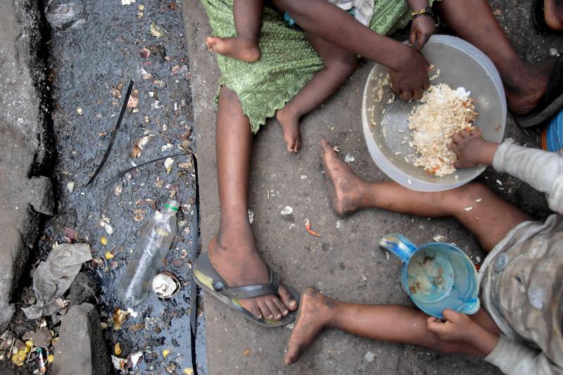 Children share a meal sitting by a sewage filled gutter in Susan's Bay slum in Freetown, Sierra Leone, November 29, 2008.