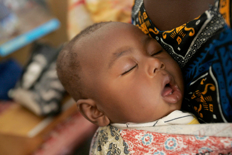 A child sleeps on his mother's back during Maternal and Child Health Week at Kabala Hospital, Sierra Leone,  Nov. 22, 2008.
