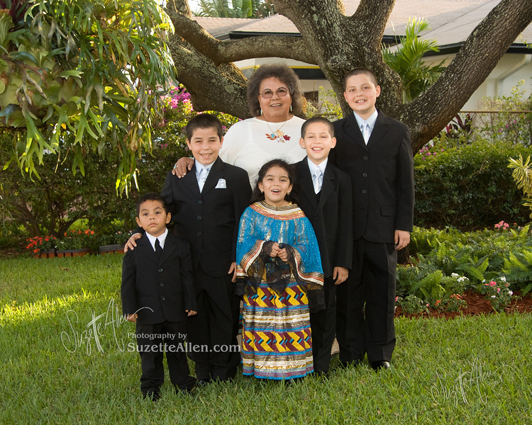 Formal wear typically is good for an indoor setting but the richness of the landscaped front yard works. The most successful part is that everyone is dressed like they are all attending the same event (all formal)  Grandma is wearing her Seminole Indian tradiitional dress here, too, which matches the little granddaughter's dress. What a great portrait that will be passed on for generations!
