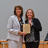 Superintendent Dr. Kara Coglianese presents a farewell plaque to former board president Jennifer Gasbarro