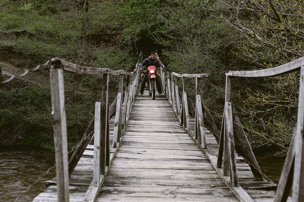 Edagrd and Anna having fun while crossing a hanging bridge with a motobike.