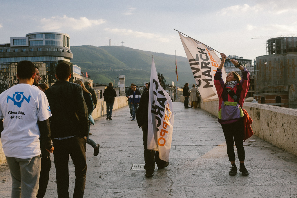 Clara waving a flag while closing to the Skopje main square.