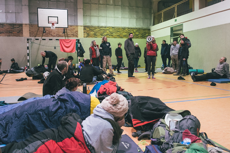 Tired marchers settled their sleeping materasses on the floor of the sport hall while Marta (Poland) from the orga team informs about further activities - documentaries show.