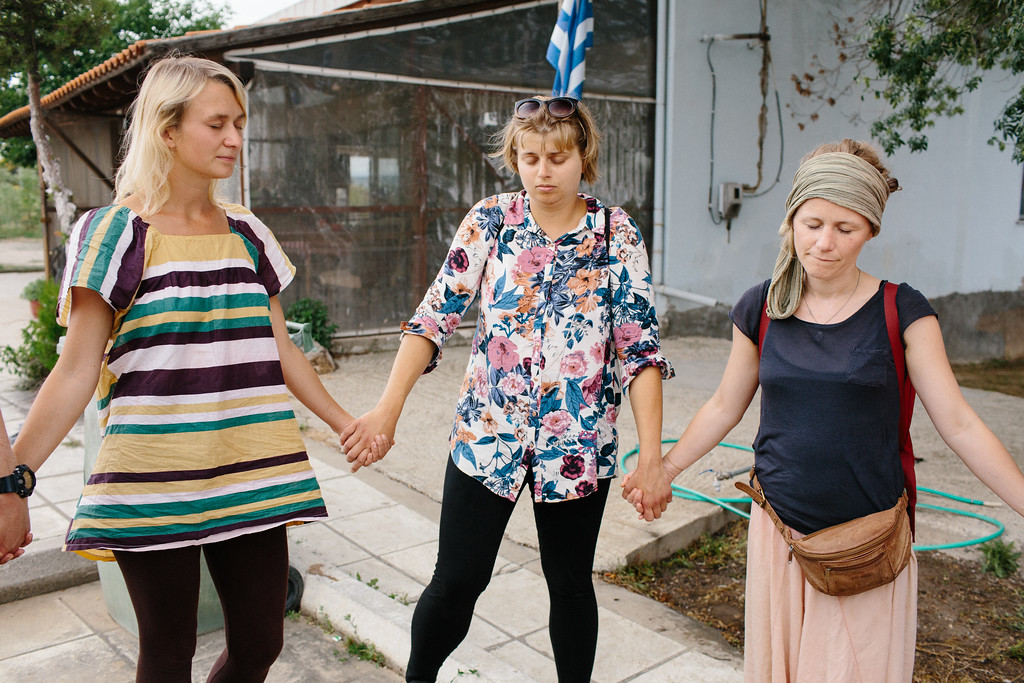 """Anna (Poland), Wiktoria (Poland) and Lisa (Germany) holding their hands and commemorating victims of the Syrian war by minute of silence during morning CMFA circle. After the marchers used to yell """"Haleb/Halab"""" (Aleppo)."""