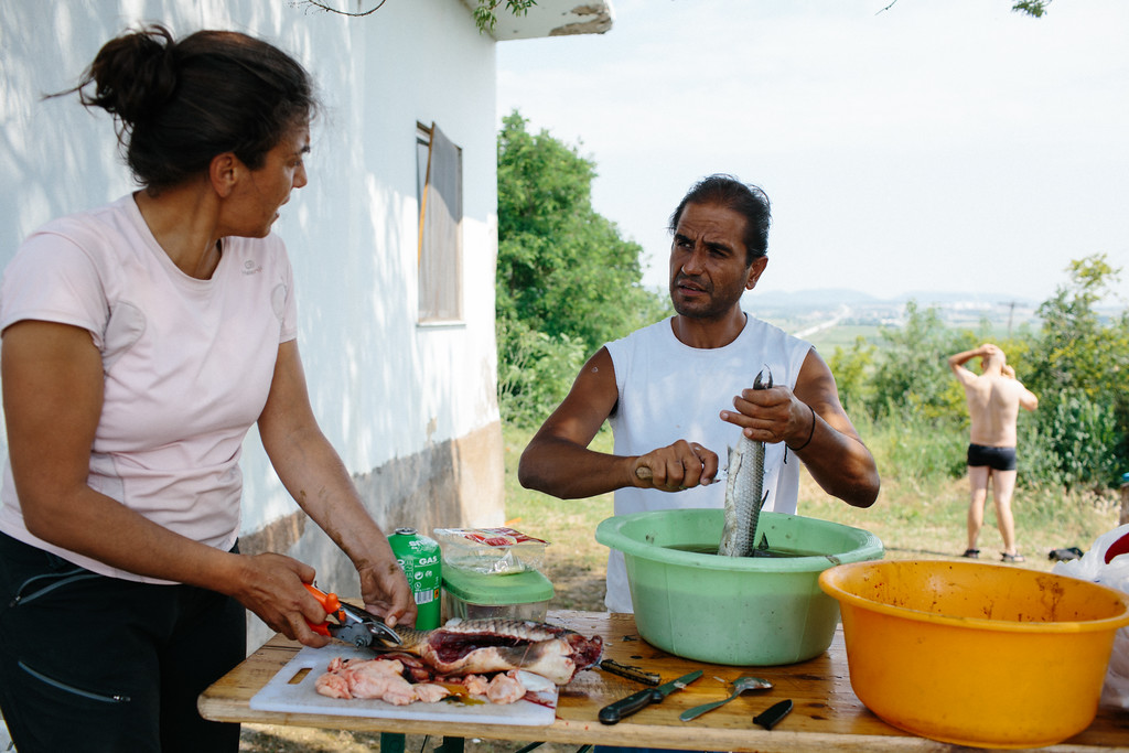 """Malika (France) and Jodi (Spain) preparing fishes that we were given two days before. We didn't have any fridge so everything should be eaten within a day, otherwise it got rotten instatntly, since temperature inside VW """"Habibi"""" storage compartment was as high as 50 degrees Celssius."""