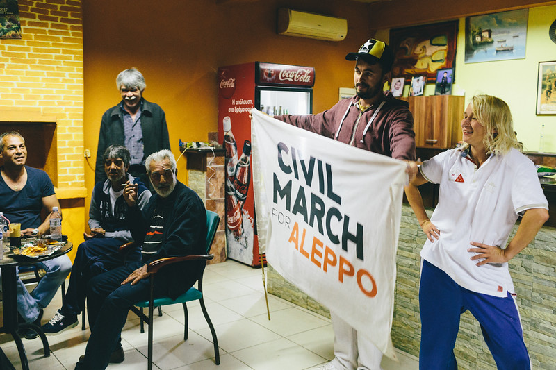 Posing to a photo with Civil March For Aleppo flag, inside Adi's cafe, Agriani, Greece.