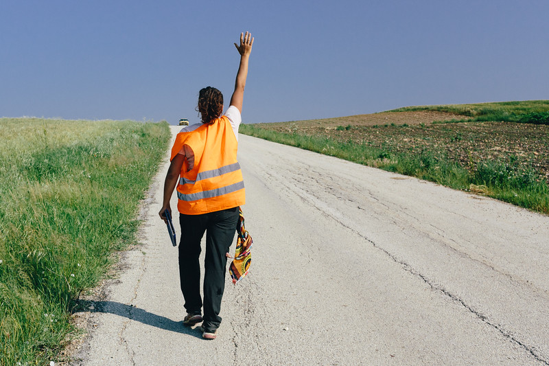 "Malika (France), ""Qeen of the March"", greets passing cars near Mani, Greece."