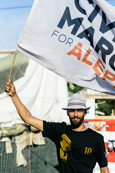 Wessam, from Syria, holding the flag of Civil March For Aleppo, during march on Lesbos (Greece).