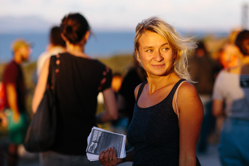Anna (Poland), during the break in One Happy Family - Community Center, Lesvosl holding cmfa leaflets.