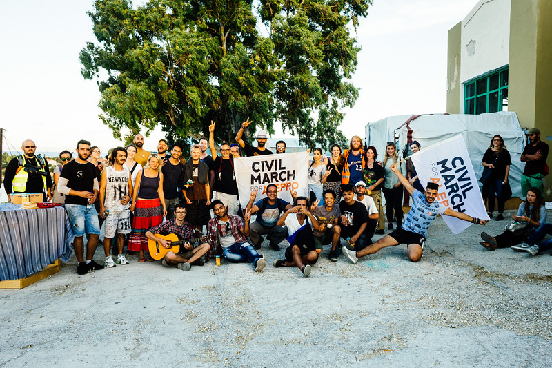 Group photo of all marchers during a break at One Happy Family - Community Center, Lesvos. They hosted us with food and beverages. Thank you!