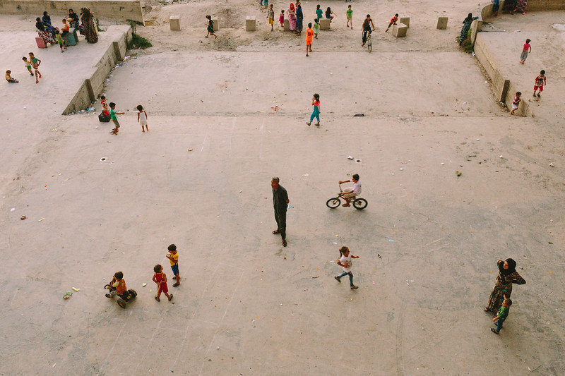 An adult among children. Syrian refugees play in the courtyard of a four-story Ouzuai complex building in Saida, Lebanon. Its home for around 1200 Syrian refugees — most of them from the same village (on of the first displaced during the revolution).