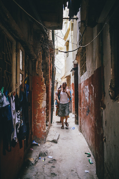 Tom (Germany) walks along a narrow street of Shatila.