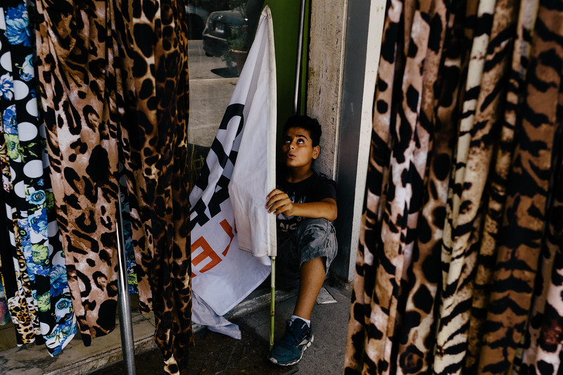 Newbie Lebanese marcher waiting with the flag in the shadow while CMFA ladies are buying their dressess for the evening event in Zico House.
