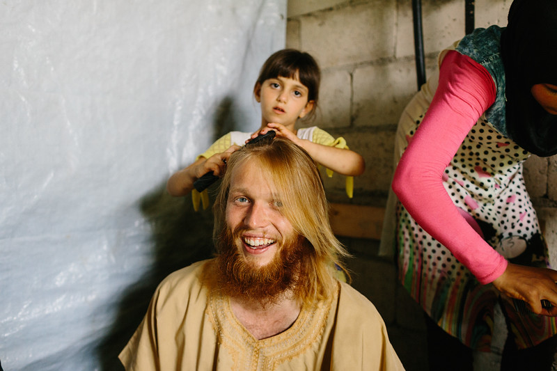 Alex (Germany) having his hair done by a Syrian girls. He also got a traditional robe and had a shower after a long day. Syrian hospitality!