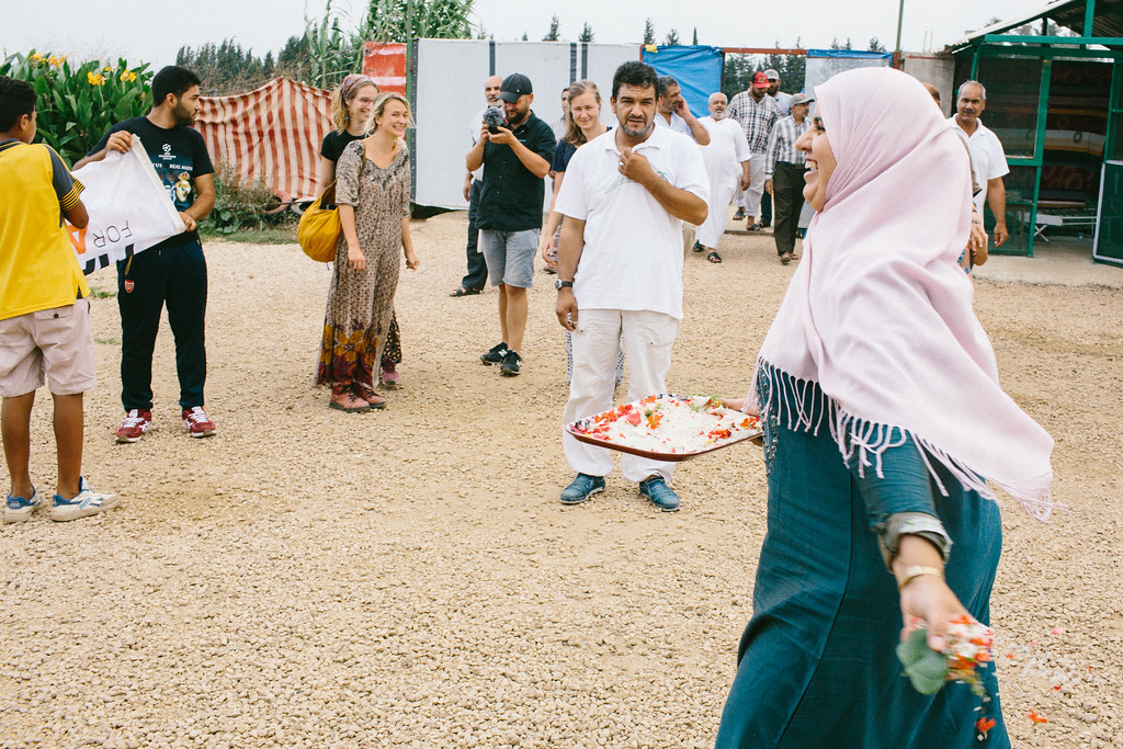 Syrian woman welcoming CMFA, throwing flower's petals, near the Malaak educational center.