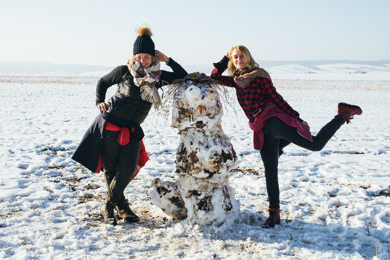Olga and Anna (both Poland) posing with a snowman.