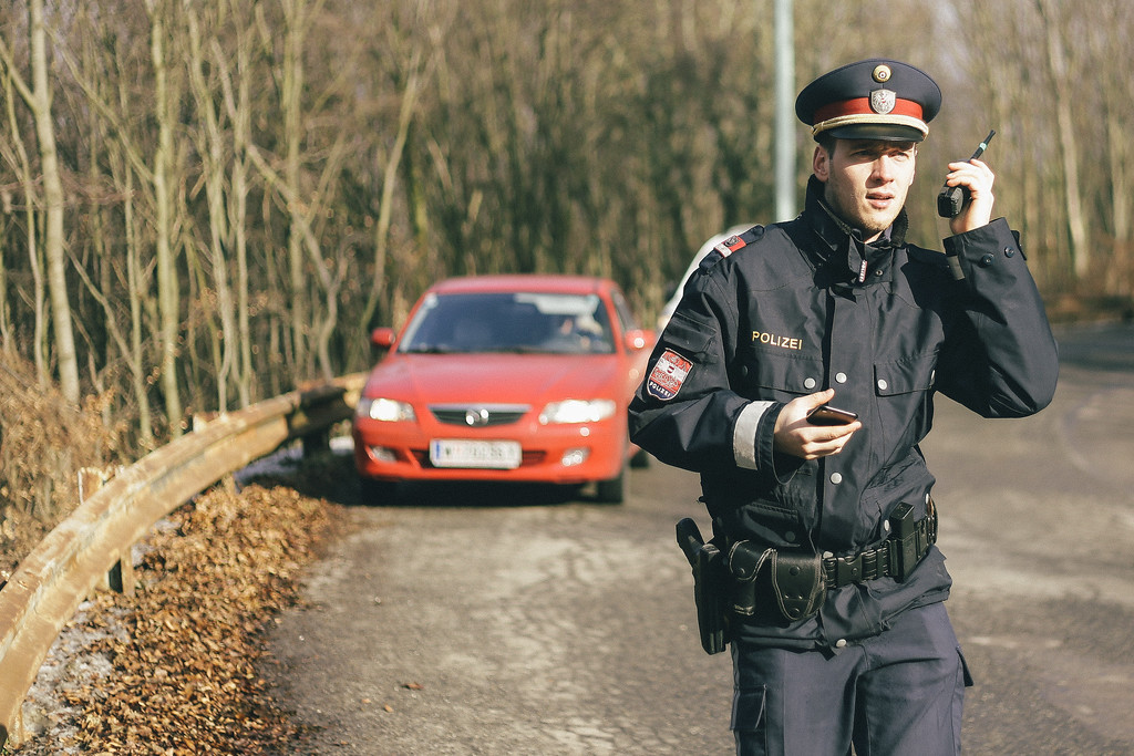 Austrian policeman securing the group.