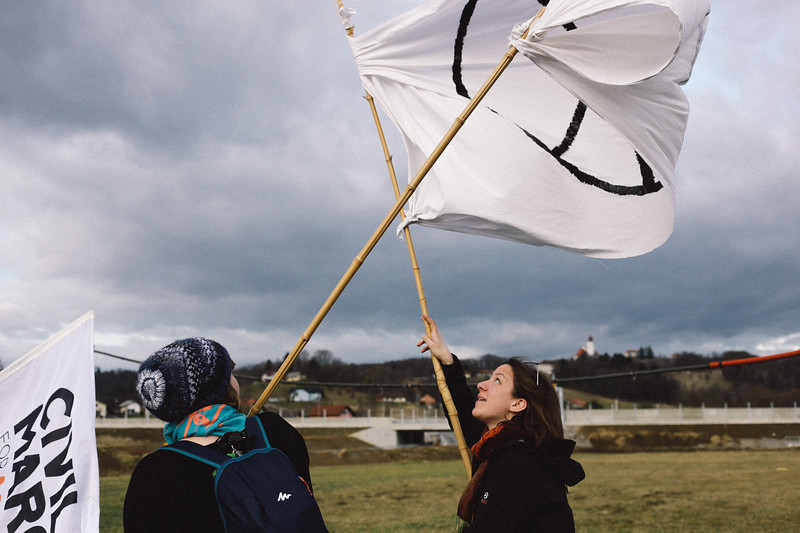 Wika and Kika (both Poland) managing a huge peace flag while stron wind is blowing.