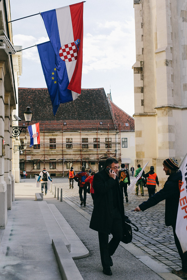 Entering Zagreb; Alex (Germany) handing a leaflet to a busy man. Zagreb, Croatia.