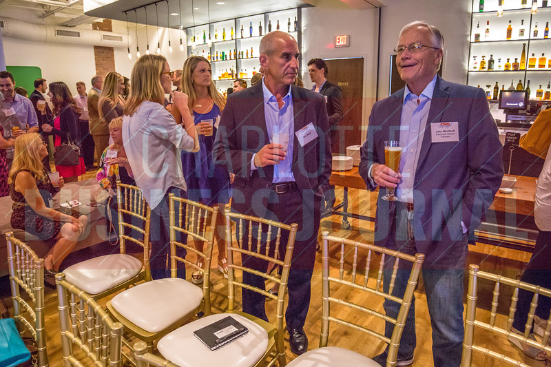 Attendees of Charlotte Business Journals CMO Unplugged event at 8.2.0 Bar, AvidXchange Music Factory network with speakers, sponsors, and other attendees before the panel gets started.