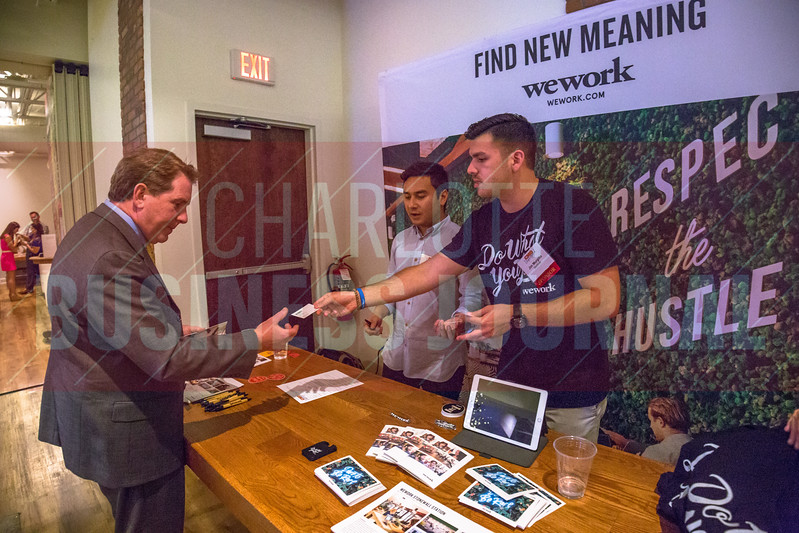Attendees of Charlotte Business Journals CMO Unplugged event at 8.2.0 Bar, AvidXchange Music Factory engage with event sponsors such as WeWork as they network after the event.