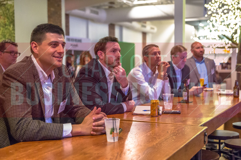Attendees of Charlotte Business Journals CMO Unplugged event at 8.2.0 Bar, AvidXchange Music Factory listen intently to the panel discussion portion of the event.
