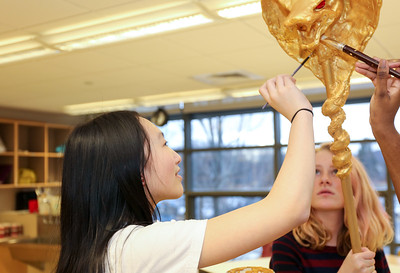 Yuxuan Lin paints a prop for Disney's Aladdin Jr. at Canton Middle School. In background is Sophia Edwards, assistant stage manager.