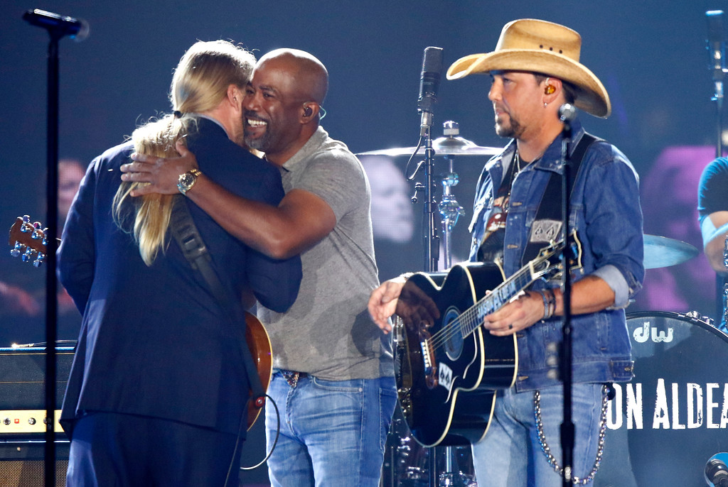 ". Derek Trucks, left, and Darius Rucker embrace as Jason Aldean looks on after performing ""Midnight Rider\"" during a tribute to Greg Allman at the CMT Music Awards at Music City Center on Wednesday, June 7, 2017, in Nashville, Tenn. (Photo by Wade Payne/Invision/AP)"