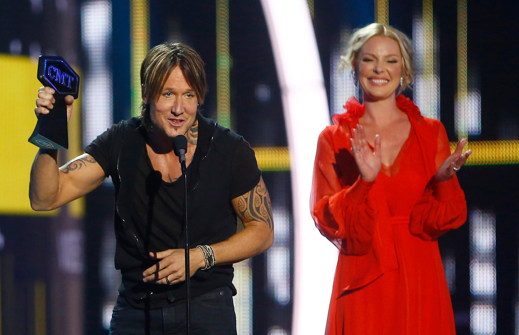 ". Keith Urban accepts the award for male video of the year for ""Blue Ain\'t Your Color\"" at the CMT Music Awards at Music City Center on Wednesday, June 7, 2017, in Nashville, Tenn. Looking on in background right is presenter Katherine Heigl. (Photo by Wade Payne/Invision/AP)"