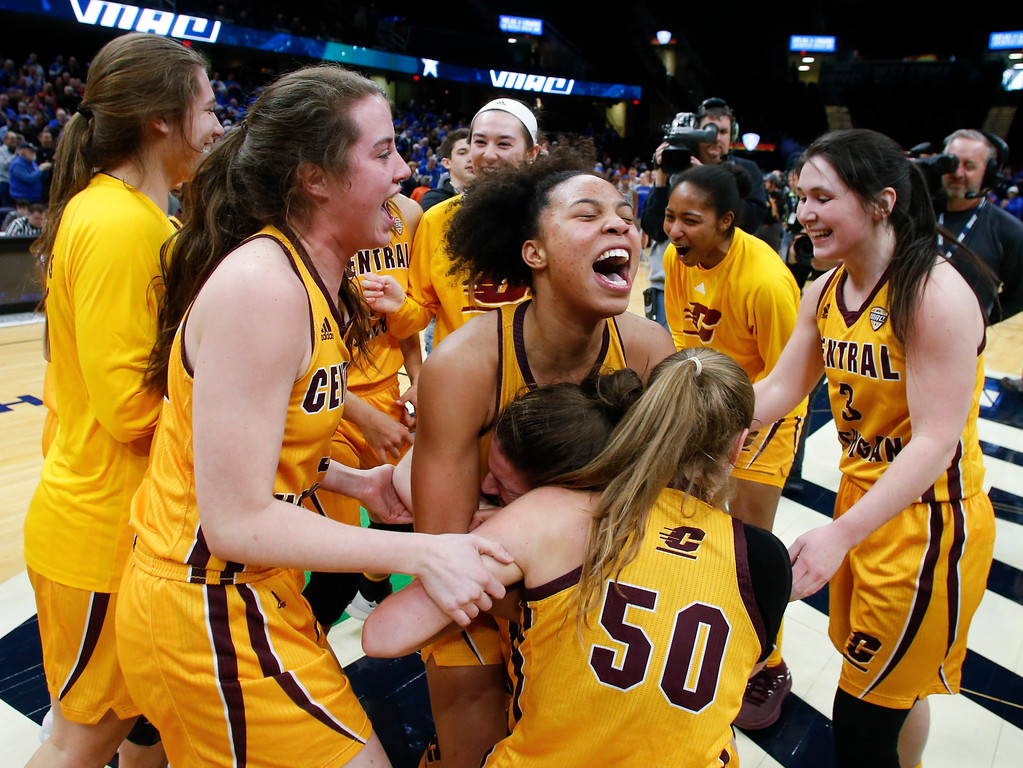 . Central Michigan forward Tinara Moore, center, celebrates with her teammates after defeating Buffalo 96-91 in an NCAA college basketball game during the championship of the Mid-American Conference tournament Saturday, March 10, 2018, in Cleveland. (AP Photo/Ron Schwane)