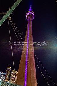 CN Tower Toronto Canada at night with purple lighting and some surrounding buildings