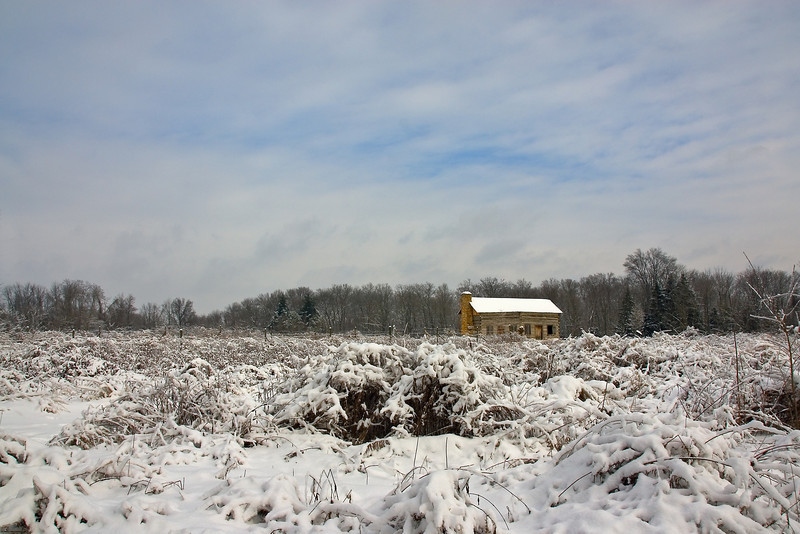 On a cold snowy winter day Abner Hollow Cabin in the fields.