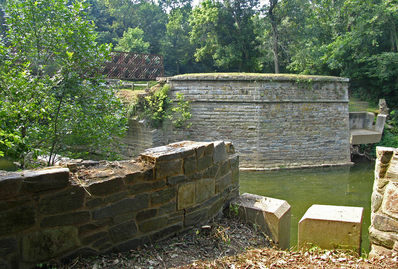 8/13/2005   In the foreground are the remains of a concrete beam bridge that was installed parallel to the aqueduct to link the severed towpath after the aqueduct collapsed in 1973. This temporary footbridge lasted only until another flood in 1976. The western side abutment for this temporary footbridge is visible across the creek next to the western wing wall