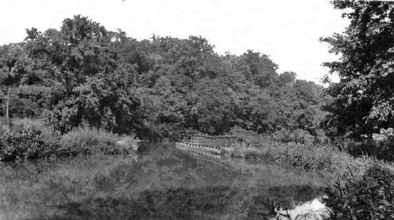 This early 1900's picture of the Catoctin Aqueduct when watered and still in use was taken from the western end. The sharp turns the canal boats negotiated before entering and after exiting the aqueduct are visible. The sag in the towpath side railing is evidence of the sagging center elliptical arch out of sight below.