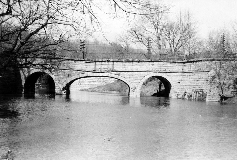 Historical picture of the Catoctin Creek Aqueduct facing the towpath side. Telegraph poles and wires and the viaduct for the B&O Railroad are visible behind the Aqueduct.The Aqueduct was known as the Swayback Aqueduct as it became progressively more deformed because of its flawed design (an ellipical center arch bracketed by two smaller circular arches).