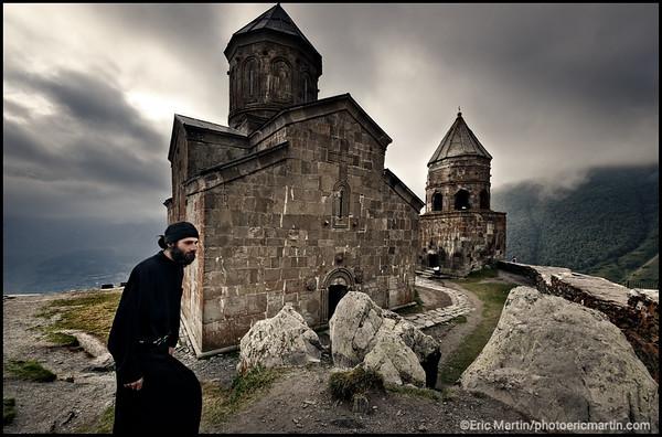 GEORGIE. Kazbegi (Stepantsminda). Andrea, un moine novice de 24 ans devant l'église de la Sainte-Trinité de Guerguétie ( ou Gergeti ) Tsminda Sameda