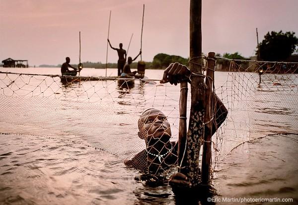 LE BENIN  Cérémonies vaudoues, éléphants gracieux, cités lacustres et plages sans fin : le Bénin, ex-Dahomey, recèle tous les envoûtements de l'Afrique. Ici, à l'ouest de Cotonou, dans la lagune de Ouidah, un pêcheur fixe ses filets avant la nuit.