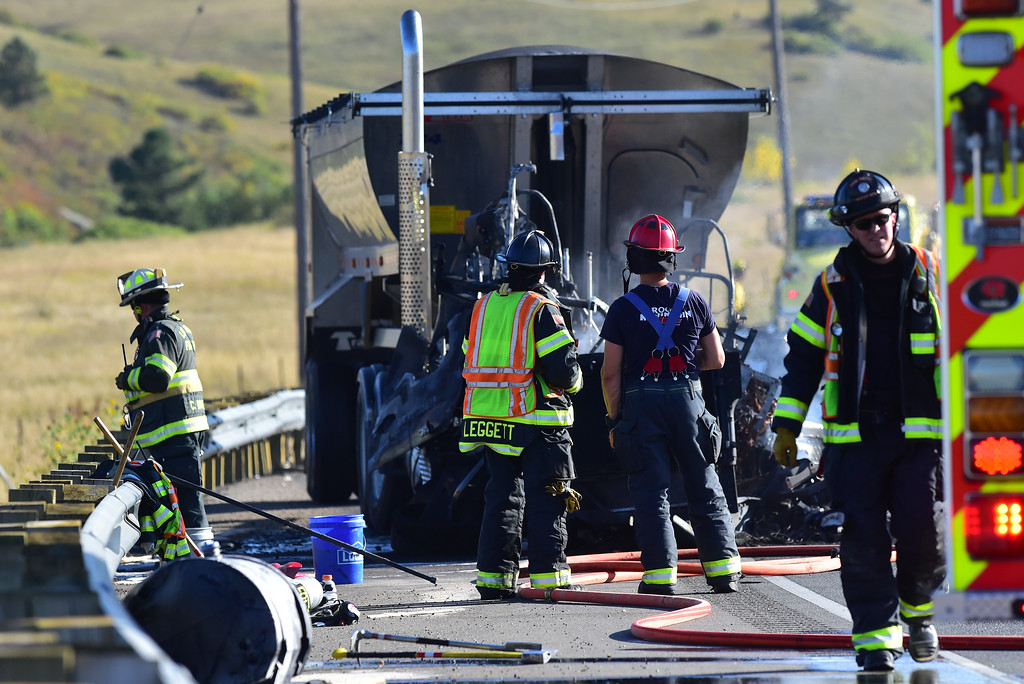 . Firefighters look over the remains of a semi-trailer truck that was involved in a fatal crash on Colorado 93 south of Boulder on Monday afternoon.  For more photos go to dailycamera.com  Paul Aiken Staff Photographer Sept 18 2017