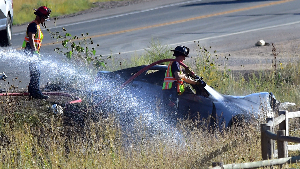 . Firefighters spray down a vehicle that was involved in a fatal crash on Colorado 93 south of Boulder on Monday afternoon.  For more photos go to dailycamera.com  Paul Aiken Staff Photographer Sept 18 2017