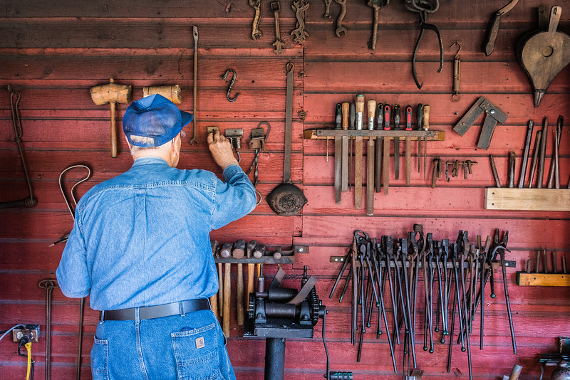 Instructor Al Briggs selects a tool from the blacksmith shop wall.  Blacksmith shop and class at the Heritage Village at Big Creek in Sturgeon Bay, Door County, WI. Photo by Len Villano.