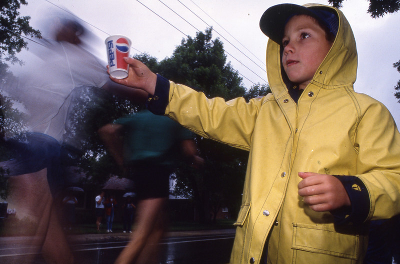 A young man hands out water cups in a raincoat during the 1992 Bolder Boulder.