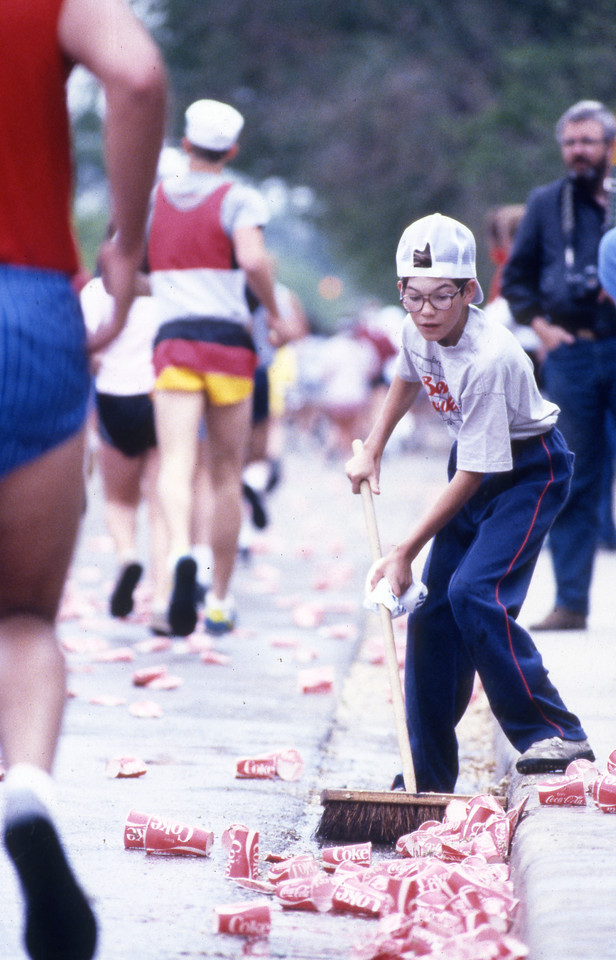 A volunteer cleans up water cups at a 1984 Bolder Boulder water station.