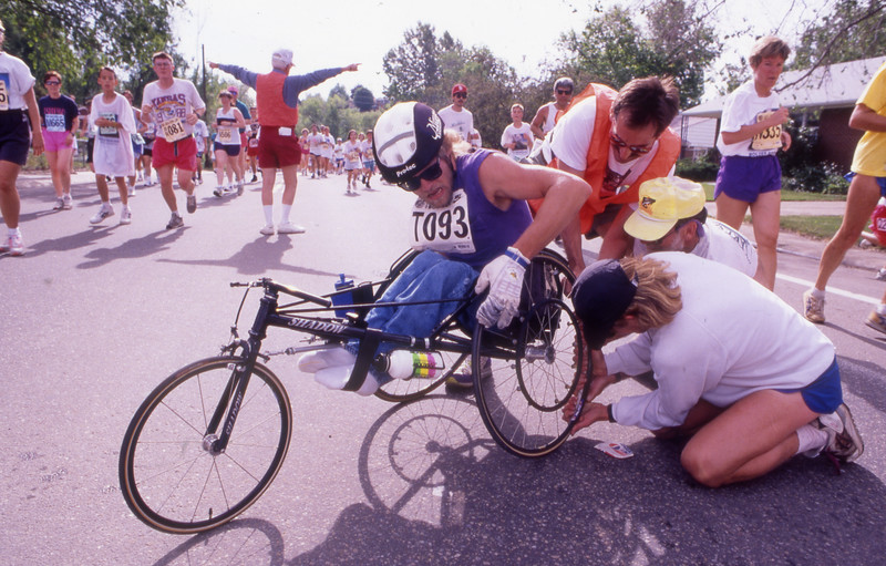 A wheelchair racer gets help from race officials and other runners during the 1993 Bolder Boulder.