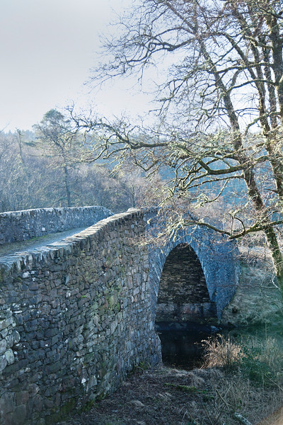 Traditional Dry Stone arched bridge over water in Scottish Highlands