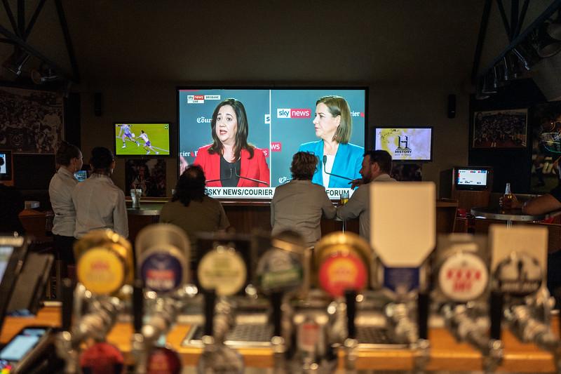People watching the debate on tv between Queensland Premier Annastacia Palaszczuk and Opposition leader Deb Frecklington. Broncos League Club, Brisbane, Queensland. Photo: Attila Csaszar