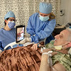 Tracey Arnauer and Lisa Blumer . A patient uses an iPad to speak to family while in isolation. <br /> Holy Name Medical Center in Teaneck, New Jersey, during the first weeks of the COVID-19 Pandemic.  04/07/2020  Photos by Jeff Rhode  Mandatory photo credit, and please use only with permission from Jeff Rhode and Holy Name Medical Center. <br /> If you need ID's or detailed captions please call 201-543-8067 or email jrhode@holyname.org