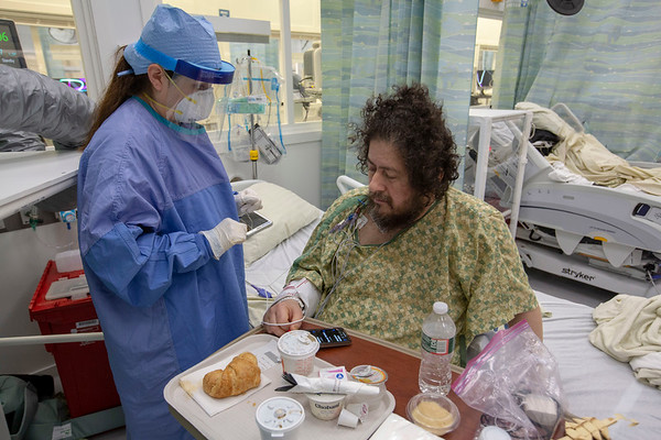 Father Christos is now able to site up on the side of the bed and eat. Photos at Holy Name Medical Center during the first weeks of the COVID-19 Pandemic. <br /> <br /> 04/15/2020  Photos by Jeff Rhode/Holy Name Medical Center.  Mandatory photo credit, and please use only with permission from Jeff Rhode and Holy Name Medical Center. <br /> If you need ID's or detailed captions please call 201-543-8067 or email jrhode@holyname.org