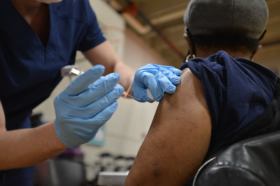 LPN Brice Headrick injects Anita Haney, 74, who showed up at Linwood YMCA for her first COVID-19 vaccination on Feb. 3.
